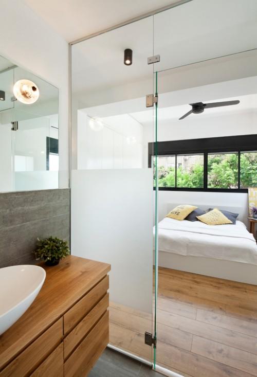 דלת זכוכית מפרידה בין אזור השינה לאזור הרחצה בחדר