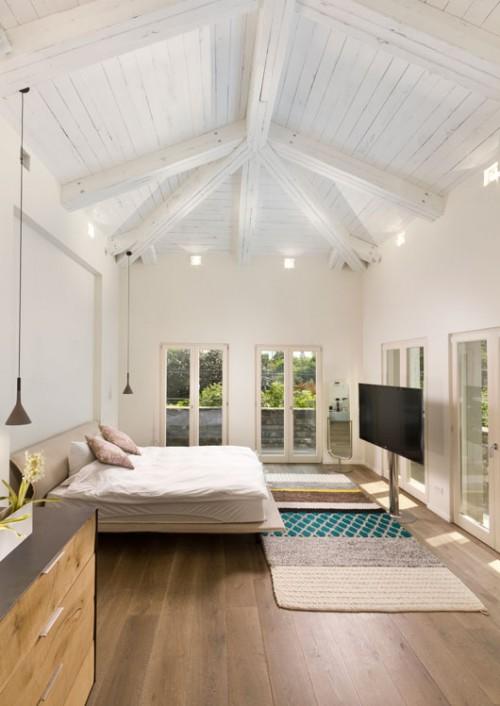 חדר הורים בבית ברמת השרון. תקרת קורות עץ גושני צבוע לבן ווש נותנת תחושה של סוויטה רומנטית. צילום: אסף פינצ'וק