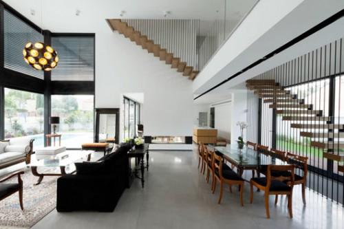 תקרת הסלון גבוהה במיוחד כדי ליצור תחושת וואו. מעל פינת האוכל נמתח גשר המשרת את הקומה העליונה. בקיר המרוחק נבנתה אח דו צדדית המפרידה בין הסלון למטבח
