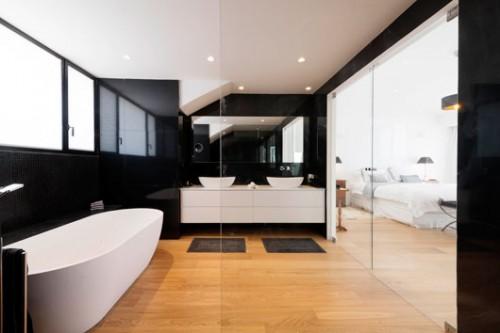 מבט מתוך המקלחון אל חדר האמבטיה ואזור השינה. זכוכית שקופה ומראות מעצימים את תחושת הגודל של החלל