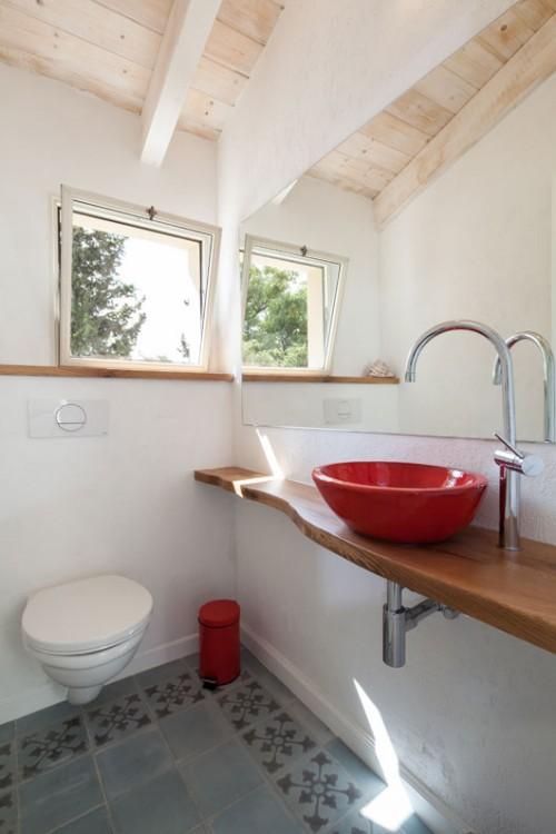 פריטים באדום ומדף עץ בגימור טבעי מוסיפים חמימות לשירותי האורחים