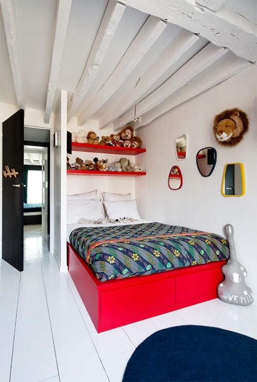 בחדרו של הבן הגדול ניצבת יחידה המשלבת מיטה ומדפים בעיצוב לבואן. על הקיר נתלו מראות בגדלים שונים ובובות פרווה חמודות הבולטות על הרקע הלבן והנקי | צילום: Francis Amiand