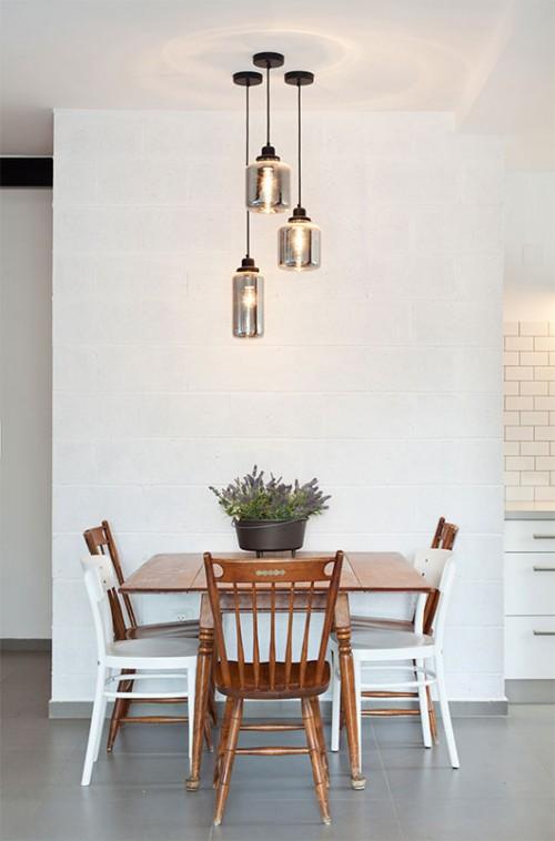 פינת אוכל ישנה שהובאה מארצות הברית על ידי סבתה של בעלת הבית הוצבה על רקע קיר לבנים חשופות שנצבע לבן. כיסאות איקאה לבנים משלימים את הכיסאות החסרים בסט | צילום: בועז לביא