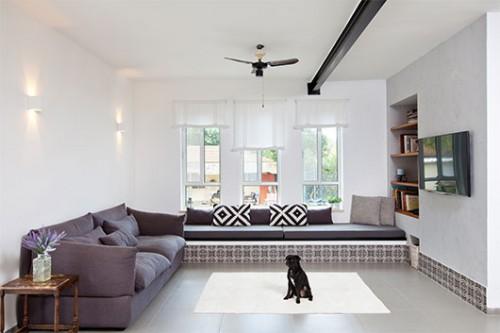 ספסל רחב מגבס, שמחליף את אחת הספות בסלון, חופה באריחים מאוירים בדוגמה מעוגלת המוסיפה חמימות לבית בלי להיות נוסטלגית או אוריינטלית