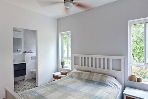 חלונות צרים וארוכים משני עברי המיטה משקיפים אל החוץ הירוק ומתכתבים עם שלושה חלונות דומים בסלון