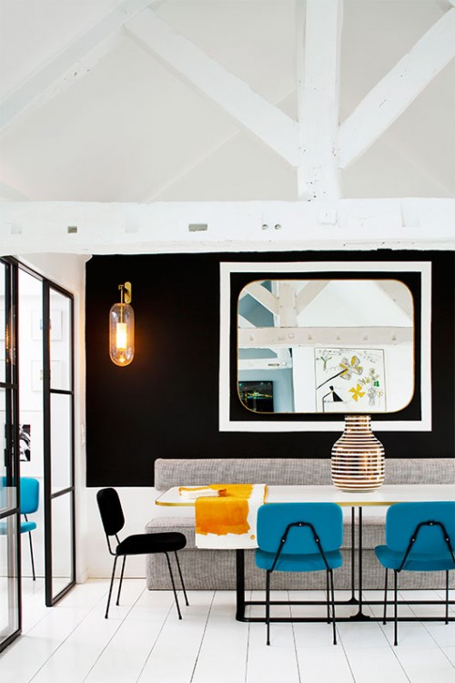 קיר פינת האוכל נצבע שחור והוא יוצר מעין נקודת מוקד. מראה בסגנון וינטג' לא רק מגדילה את החלל אלא גם משקפת את עבודת האמנות שתלויה ממול | צילום: Francis Amiand