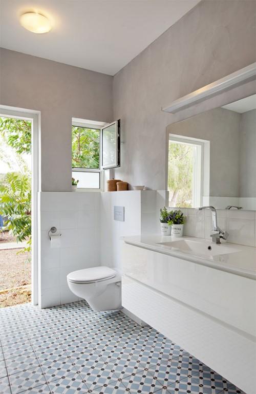 האריחים הלבנים הפשוטים וטיח וגה אפור שמעליהם מעניקים רקע ניטרלי לרצפה המאוירת בחדר הרחצה | צילום: בועז לביא