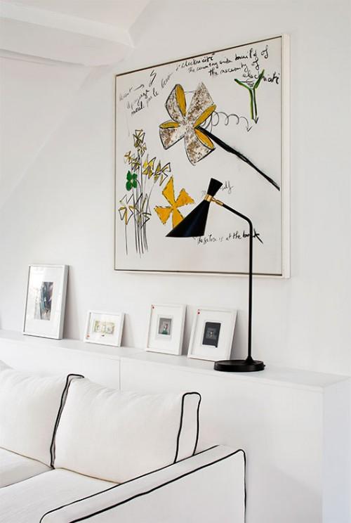 עבודת אמנות של האמן הצרפתי פבריס איבר, המתאפיינת בקו קליל ואיורי, נתלתה מעל ספה בעלת קווים גרפיים | צילום: Francis Amiand