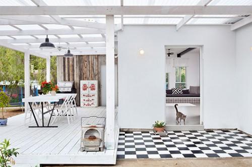 המרפסת הנמתחת לאורך הבית רוצפה בדק עץ וחופתה בפרגולה שנצבעה בלבן – מעשה ידיו של בעל הבית | צילום: בועז לביא