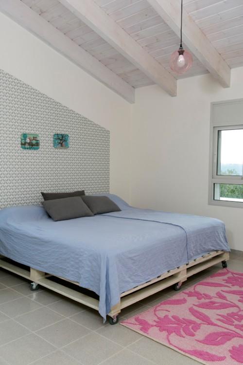 טפט מאויר שנחתך בקו אלכסוני, מדגיש את התקרה המשופעת בחדר ההורים   צילום: שירן כרמל