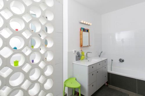 חדר הרחצה רחב במיוחד ומשרת את כל בני המשפחה. קיר מאריחי משרבייה מעוגלים המפריד בין המקלחון לשירותים מוסיף קלילות ואווריריות לחלל   צילום: שירן כרמל