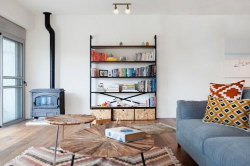 הספרייה בסלון נבנתה בהזמנה ועליה פריטים שלוקטו במיוחד על ידי המעצבות, כמו גם עבודות נייר של בעלת הבית   צילום: הגר דופלט