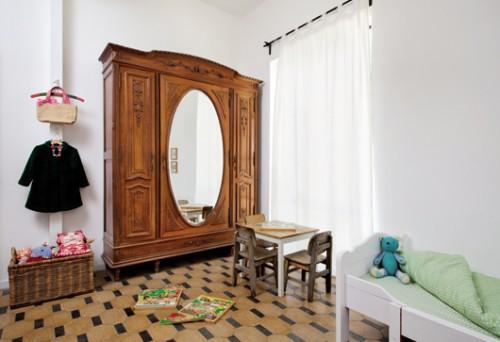 חדר הבנות מתכתב עם הקו העיצובי של הבית במרצפות הישנות ובארון בגדים עתיק. האווירה הילדית מתקבלת מצעצועים ומפריטים צבעוניים. צילום: בועז לביא
