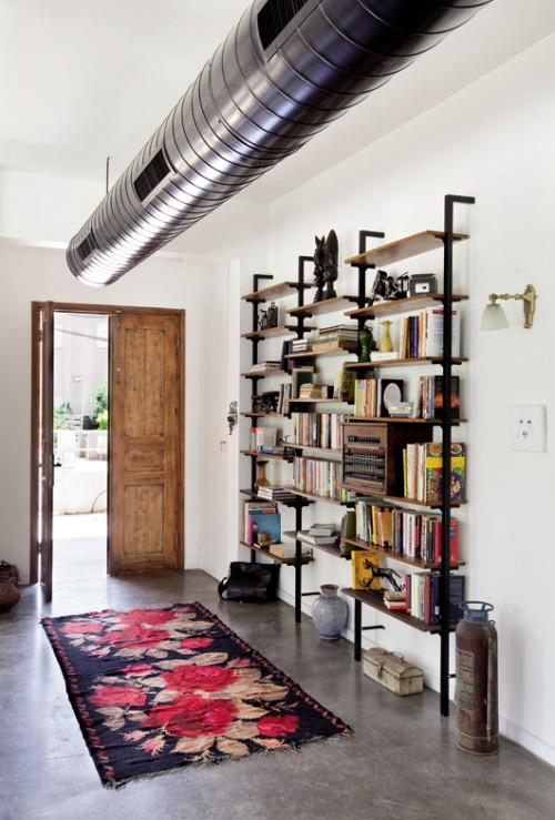 תעלת המזגן התעשייתית, דלת העץ מפירוק, רצפת הבטון המוחלק והספרייה הישנה מגדירות כבר בכניסה את אופי הבית. צילום: בועז לביא