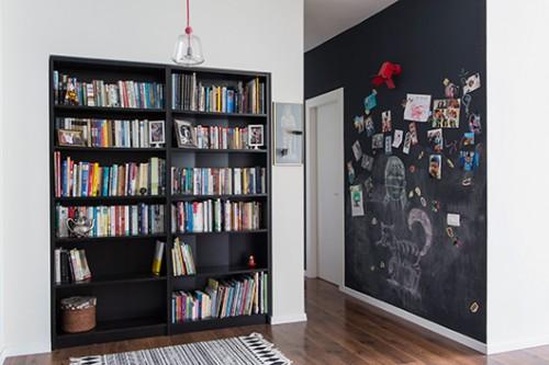 ספרייה ששובצה בקירות הגבס המקנים לה מראה יותר מתוחכם, מצדה השני, קיר המעבר שהפך למרכז פעילות בזכות שימוש בצבע לוח מגנטי | צילום: איתי בנית