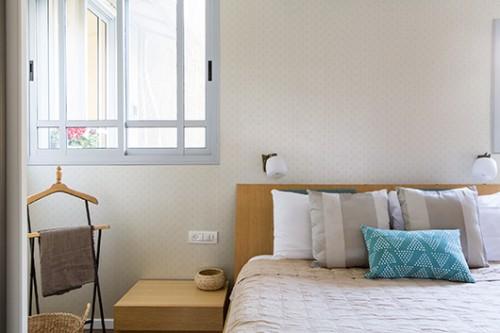 חדר שינה הורים. השימוש בטפט (גולדשטיין) משדר רכות ומשמש רקע ומסגרת למיטה | צילום: איתי בנית