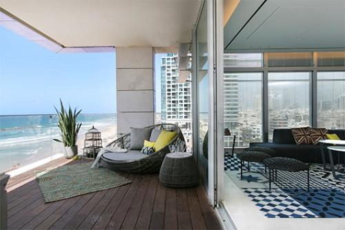 קווי המתאר העגולים בריהוט יוצרים קשר סגנוני בין הסלון והמרפסת. בחירת החומרים והריצוף מבדילה בין שני האזורים המופרדים פיזית בדלת זכוכית גדולה   צילום: שירן כרמל
