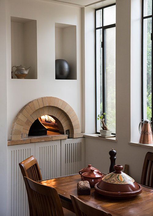 הבית של ערן חם ומזמין. בית פתוח עם חצר גדולה לאירוח ותנור אבן במטבח שמסמל את מדורת השבט שהוא מקפיד לטפח. ציורים של אביו, יוסף רולס, מעטרים את הקירות ברחבי הבית   צילום: גלעד רדט