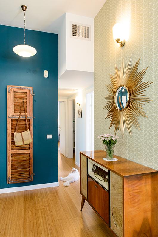 על קיר בגוון ירוק־כחול נתלתה דלת ישנה שנרכשה בשוק הפשפשים ומסתירה ארון חשמל | צילום: אדריאן דודה