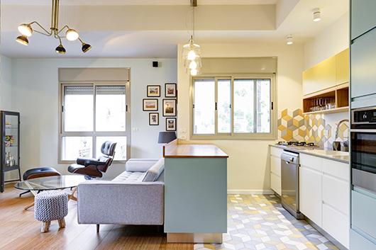 החלל הציבורי מורכב ממטבח וסלון. ההפרדה ביניהם היא סגנונית ונעשתה באמצעות ריצוף וגוונים | צילום: אדריאן דודה