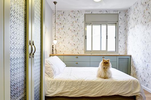 חדר השינה שומר על אחידות בגוונים עם הדירה כולה. טפטים מצוירים, גופים דקורטיביים מוזהבים וגופי תאורה תלויים מוסיפים נגיעה רומנטית | צילום: אדריאן דודה