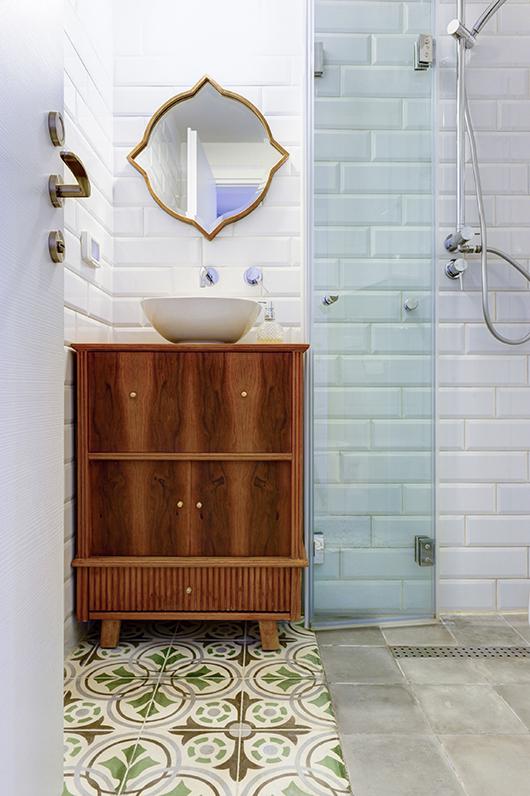 חדר הרחצה הצמוד לחדר השינה הראשי מעוצב בגוני אפור, חום וירוק בטקסטורות ודוגמאות שונות | צילום: אדריאן דודה