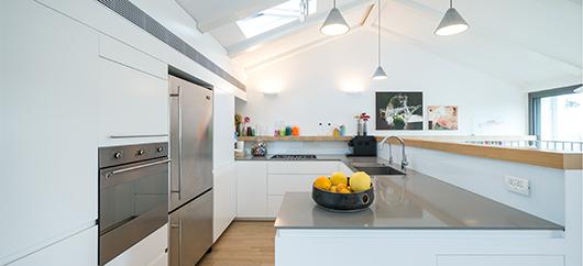 המטבח. גג דמוי רעפים יוצר תחושה של בית פרטי. ברקע ציורים של נעמי מנדלו | צילום: איתי סיקולסקי