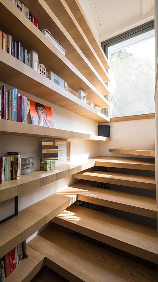 גרם המדרגות מייצר חלל נוסף – הספרייה – ומשמש תעלת אור טבעי לכל הבית | צילום: איתי סיקולסקי