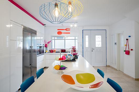 במטבח הלבן והמינימליסטי שהגיע עם הבית נוספו נגיעות צבע בדמות גופי תאורה בעיצוב גריב, כיסאות בר, קונטור של צבע מעל הארונות ומסביב לדלת ואביזרים שונים   צילום: עוזי פורת