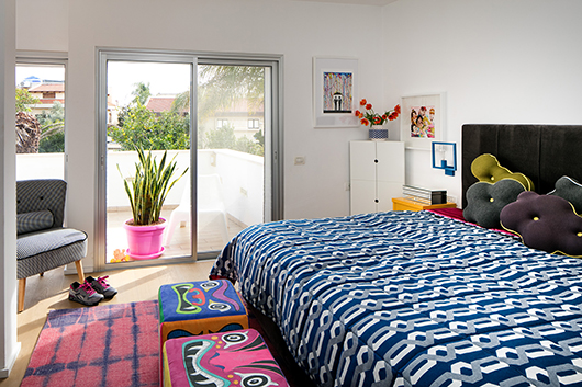 חדר השינה של ההורים תואם את שפת העיצוב בבית כולו ומציע חוויה צבעונית ושמחה לבני הזוג   צילום: עוזי פורת