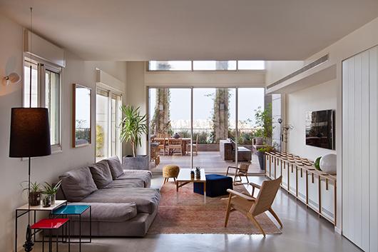 ריהוט בסגנון יפני ושנות ה-60 בגוני עץ ולבן מותיר מקום לצבעוניות שמגיעה בעיקר מהמרפסת | צילום: בועז לביא