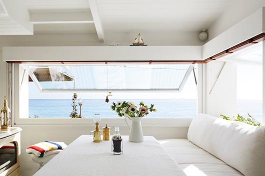 ספה רחבה בעיצוב המתכננים יוצרת פינת אוכל רגועה מול הנוף בחלל המרכזי   צילום: Francis Amiand