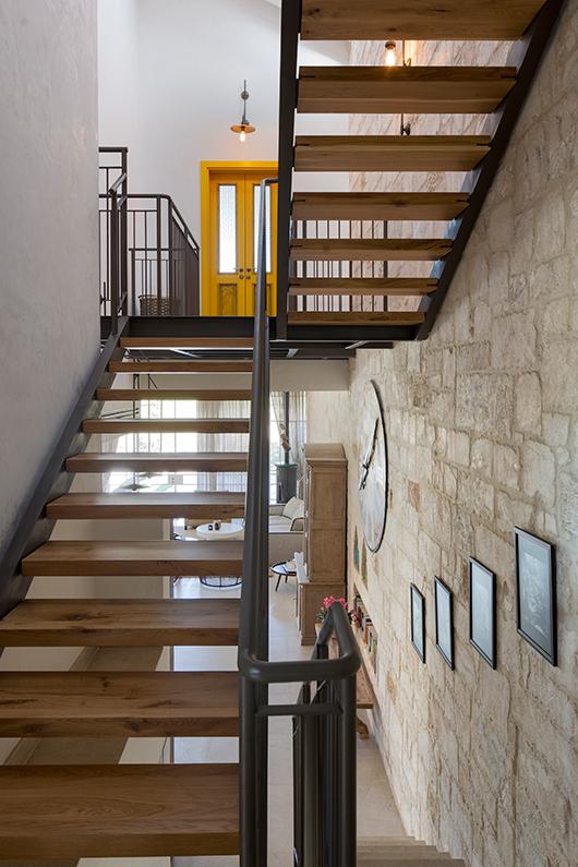 גרם מדרגות מעוצב ממתכת ועץ טבעי מחבר בין חמשת המפלסים בצורה קלילה. בסופו דלת צהובה רחבה המובילה ליחידת ההורים | צילום: שי אפשטיין
