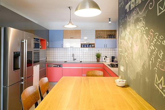 המטבח משלב מערך של תאים פתוחים וסגורים המחופים במשטחי פורמייקה בשישה גוונים שונים | צילום: אדריאן דודה