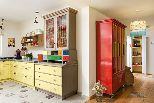 ארון מתכת (מדפי לגרדיה) במעבר בין החלל הציבורי לפרטי, וארון המטבח מעץ (RAFF בקיבוץ מעיין צבי) ששולבו בו וילון בד עם הדפס עשיר (דנדו) ומגירות צבעוניות | צילום: שירן כרמל