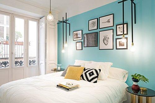 חדר בעיצוב אורבני: קיר כוח דומיננטי בצבע תכלת, קולאז' צילומים אקלקטי בגוונים של שחור ולבן. את התחושה האורבנית משלימים גופי התאורה העשויים מצינורות שחורים עם נגיעות זהב   צילום: Luis Beltran