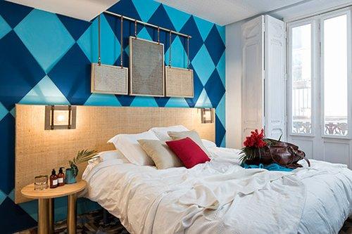 חוק הטרנדים השלובים: חדר המשלב את הטרנד האתני עם הטרנד הגיאומטרי. בעוד הקיר שמאחורי המיטה צבוע במעוינים כחולים ותכלת גדולים, עבודת האמנות וראש המיטה רופדו בבד יוטה טבעי   צילום: Luis Beltran