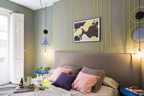 חדר שלוקח את האורבניות לקצה: כל הקירות נצבעו באפור כהה, שזהה לצבע גב המיטה, ועל גבי הקירות נתלו מסגרות מלבניות סימטריות ודקורטיביות בצבע צהוב ניאוני   צילום: Luis Beltran
