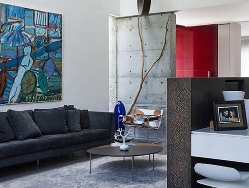 מעל הספה נתלה ציור שמן גדול בגוני כחול של הצייר אבני שמעון, המתכתב בגווניו עם קבוצה של כדי חרס ענקיים בכחול עז | צילום: עמית גושר