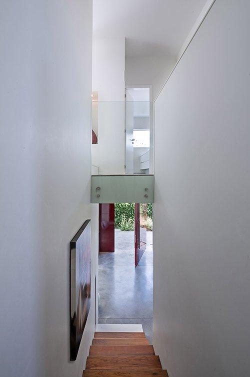 מבואות פתוחות המחברות בין חדרי השינה בקומה העליונה התחומות בקירות זכוכית מייצרות קשר עין בין הקומות ומחדירות הרבה אור ואוויר לקומה העליונה | צילום: עמית גושר