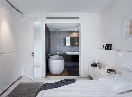 חדר הרחצה הפתוח בסוויטת ההורים, שנצבע אף הוא באפור כהה, מאפשר להשקיף אל צמרות הברושים גם בעת ישיבה באמבט | צילום: עמית גושר