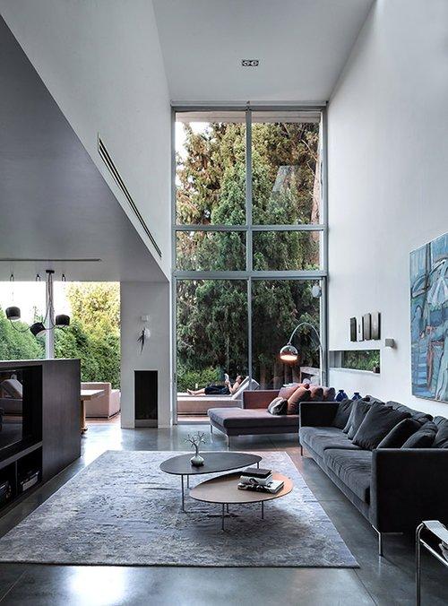 ויטרינת זכוכית ענקית בגובה שתי קומות בסלון המשקיפה אל שדרת הברושים העתיקה בחצר, שהייתה אחד הגורמים המובילים בהחלטה לרכוש את הבית | צילום: עמית גושר