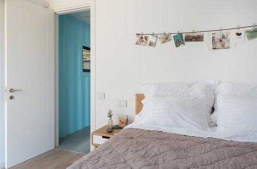 לחדרי השינה נבחרה צבעוניות מתונה הבאה לידי ביטוי בנקודות צבע בודדות על רקע גווני עץ ולבן | צילום: גלית דויטש