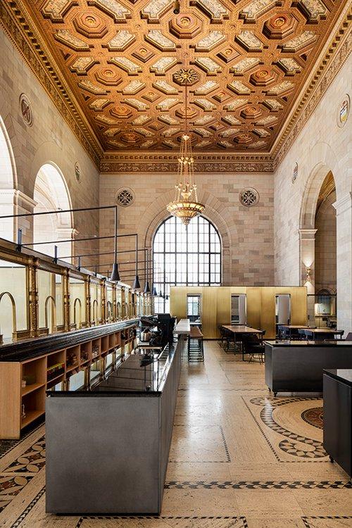 העמדות של פקידי הבנק נותרו על כנן כשהן חוצצות בין מרחב הקפה לחדרי הישיבות, מהוות עדות למורשת של המקום | צילום: Adrien Williams