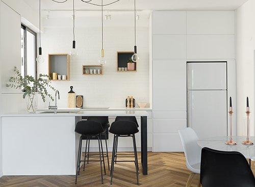 מטבח קטן אך פונקציונלי עם גופי תאורה מינימליסטיים וארונות שממקסמים את שטחי האחסון | צילום: גדעון לוין