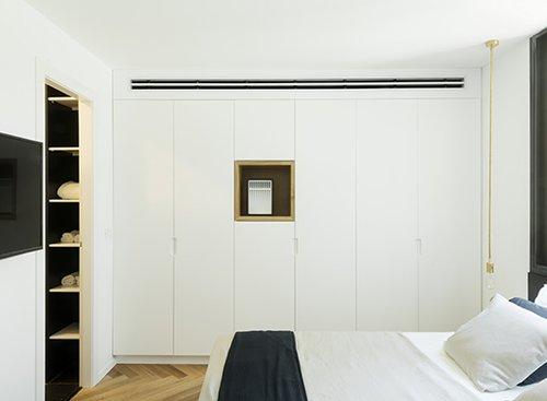 ארונות הקיר בחדרי השינה מסתירים קיר אלכסוני. בכל מקום אפשרי תוכננו נישות | צילום: גדעון לוין