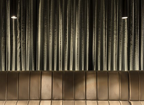 ניגוד בין האבן האמורפית לקווים הישרים בבר, בספסל ישיבה ארוך, בווילונות החשמליים ובגופי תאורה דמויי גליל | צילום: עודד סמדר