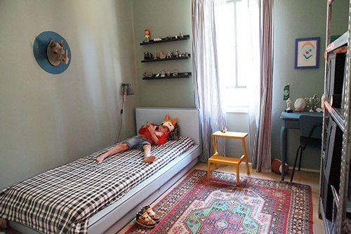 הקירות בחדר של אבינועם נצבעו בצבע קודר יחסית למקובל בחדרי ילדים, אך הוא מספק רקע הולם לאוספים הצבעוניים ונוצר מראה נעים | צילום: שרון ברקת