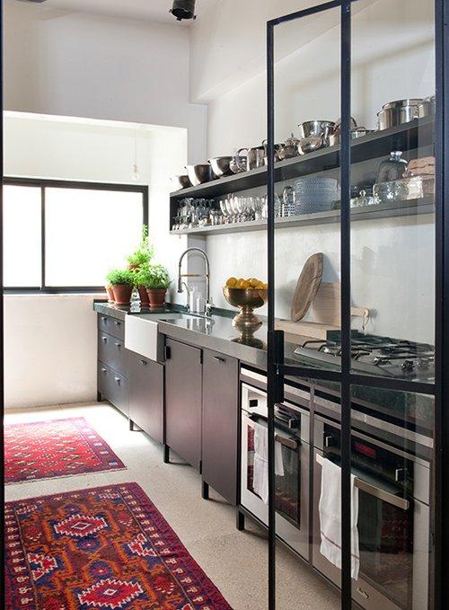 שני שטיחים אפגניים שונים בעבודת יד מכניסים אווירה חמה וביתית למטבח שחור ותעשייתי | עיצוב פנים: סטודיו GOLANALON | צילום: גלית דויטש
