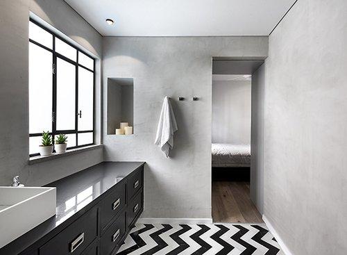 רצפת חדר הרחצה של ההורים מורכבת משני סוגי אריחי שיש בשחור לבן שהונחו בסגנון פיש־בון | צילום: עמית גושר